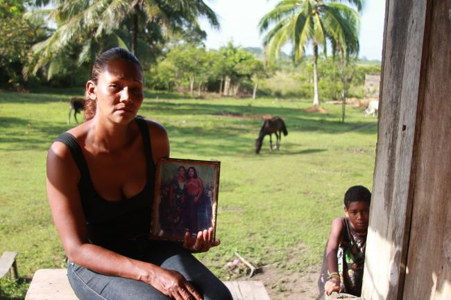Marlene Jackson holds a photo of her sister, Juana, who was shot in the heart and killed when she was six months pregnant in a joint Honduran-DEA operation. (Photo by Kaelyn Forde, Ahuas, Honduras, July 2012).