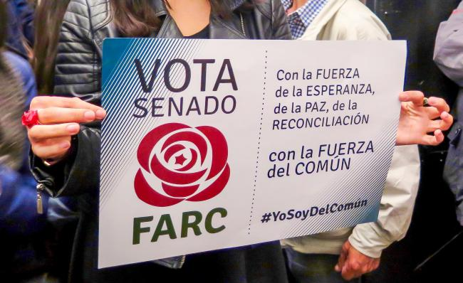 A woman holds a FARC Senate poster at the launch of the party's new headquarters in Bogotá. (Photo by Emma Shaw Crane)
