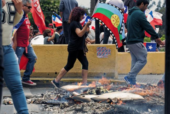 A demonstrator carries the Mapuche flag in a march in San Antonio, Chile, on November 12, 2019. (Photo by Vivian Morales/Flickr)
