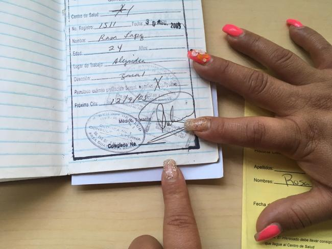 Samantha shows a page from the health booklet that was used to track the results of her regular police-enforced sexual health checks. She and her colleagues organized to get the practice outlawed in 2012 (Photo by Katie Schlechter).