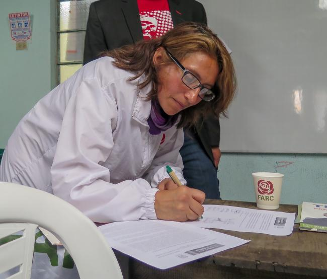 Valentina Beltrán (Luz Mery López), a former combatant and House of Representatives candidate in Bogotá signs a pact with victims of the armed conflict in a peripheral neighborhood. (Photo by Emma Shaw Crane)