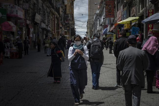 A young woman walks as she wears a medical mask as a precaution against the coronavirus (Covid-19) in a Boulevard in downtown La Paz, Bolivia on March 13, 2020. A few days later Bolivia´s interim president mandated a Nationwide lockdown until April 15 to avoid the spread of the virus in the country and suspended Presidential Election until September.