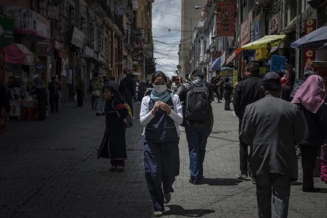 A woman wears a medical mask as she walks in downtown La Paz, Bolivia, on March 13, 2020. (Photo by Marcelo Pérez del Carpio)
