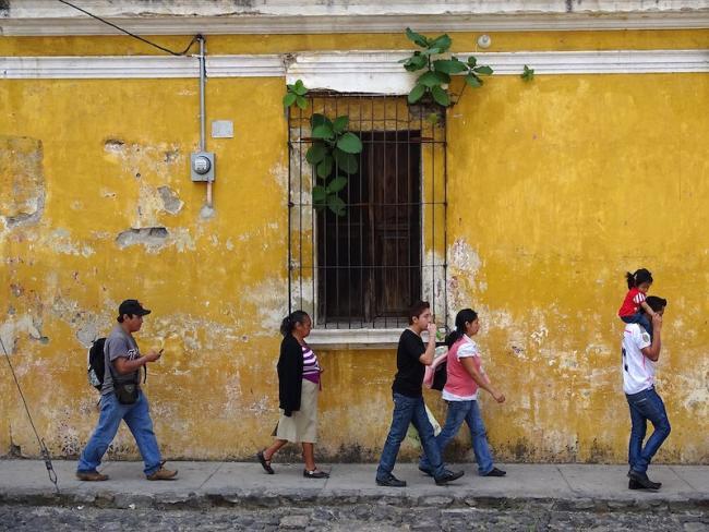 Pedestrians walk on the street in Antigua, Guatemala. (Adam Jones/Wikimedia)