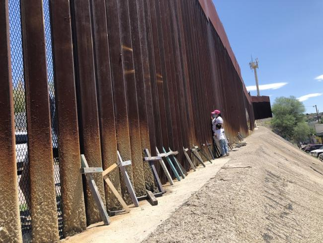 """A mother and child peer through the border wall at the otro lado (the """"other side"""" in the U.S.) with crosses memorializing migrants who lost their lives crossing in August 2020."""
