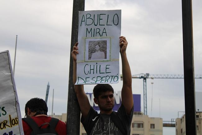 """During the 2019 protests, a demonstrator holds up a sign reading """"Look grandfather, Chile woke up"""" (José Miguel Cordero Carvacho)"""