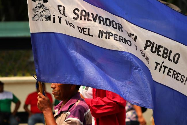 "A person carried a flag reading, ""El Salvador of the people, not of the empire or its puppets."" (Photos by CISPES)"