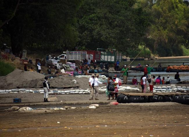 A National Guard member (left) and immmigration agents (center) on the banks of the Suchiate River in Chiapas, Mexico, while deployed in response to a migrant caravan. (Jorge Choy-Gómez)