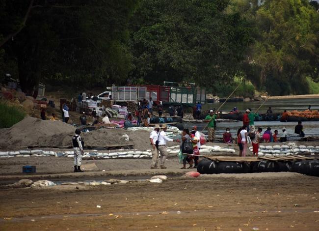 Un miembro de la Guardia Nacional (izquierda) y agentes de inmigración (centro) a orillas del río Suchiate en Chiapas, México, mientras estaban desplegados en respuesta a una caravana de migrantes. (Jorge Choy-Gómez)