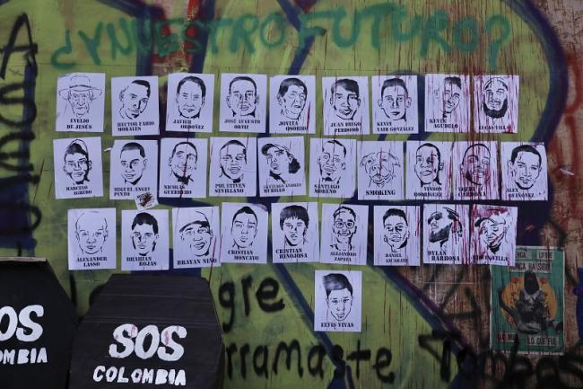 Posters of protesters who have died during demonstrations cover the walls of the Heroes Monument in Bogotá, May 12, 2021. (Christina Noriega)