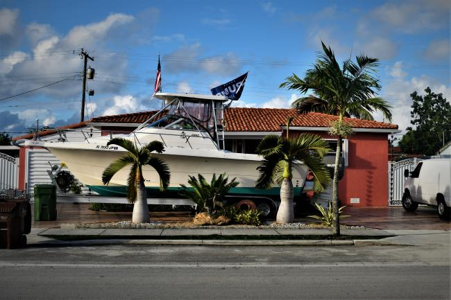 A boat adorned with a Trump flag and U.S. flag sits outside a home in Hialeah. (Ariana Hernandez-Reguant)