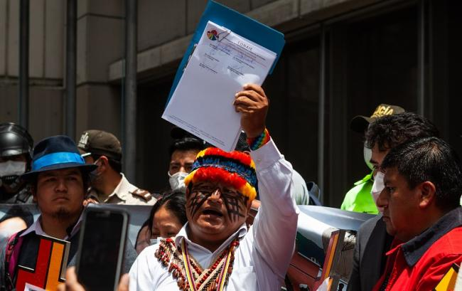CONAIE's president Jaime Vargas holds up the lawsuit on behalf of victims in front of the national prosecutor's office in Downtown Quito on Indigenous People's Day. (Vincent Ricci)