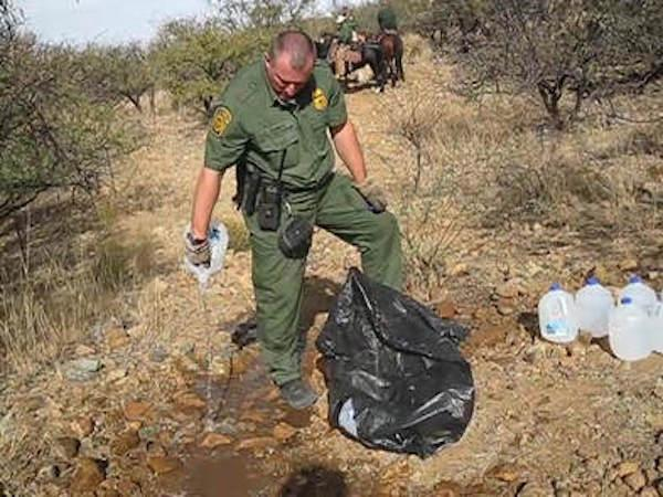 A U.S. Border Patrol agent pours out lifesaving humanitarian aid in the Sonoran Desert. (Photo by No More Deaths)