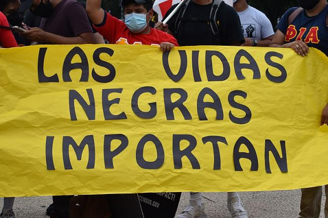 """BLM protests occurred across the globe last year, a reminder that the fight for Black lives is needed everywhere. Here, a protester in the United States holds a sign proclaiming """"Black Lives Matter"""" in Spanish. (Park Miller, Wikimedia Commons)"""