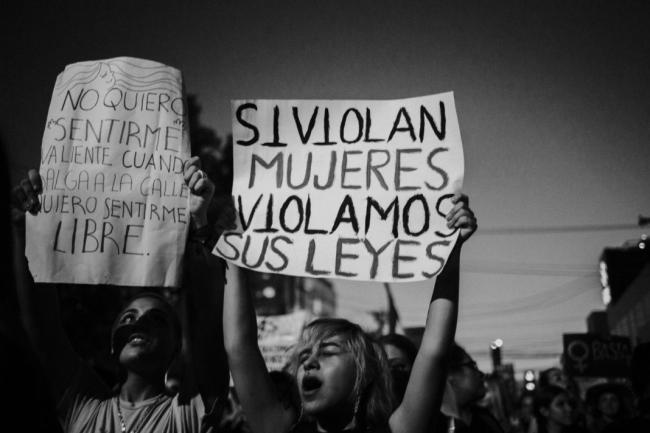 "A woman carries a sign reading, ""If you violate women, we violate your laws."" (Photos by Laura Álvarez)"