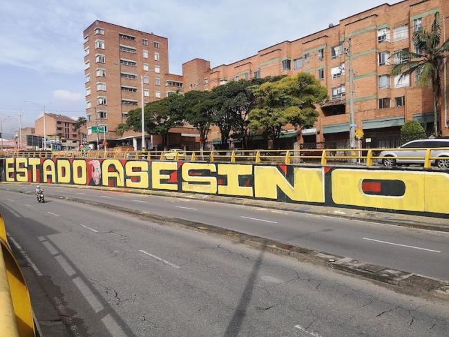"""""""Estado Asesino"""" mural located on Avenue 80 at the top of Calle San Juan, Medellín, May 2021. The mural was painted during the national strike as an act of protest against deadly violence at the hands of state forces. (XalD / Wikimedia)"""