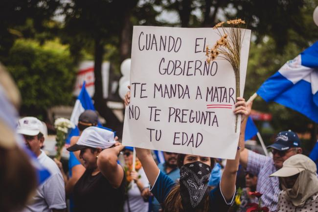 """When the government sends you to  kill, they do not ask you how old you are."" A woman during the March of the Flowers on June 30, 2018 (Photo by Mauricio Valenzuela)."