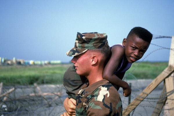 A marine carries a Haitian refugee child at Camp McCalla in Guantánamo Bay in 1992 (US Coast Guard/Wikimedia Commons)