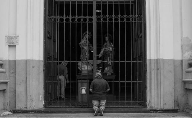 "A woman praying in her knees. Churches and temples remain closed for quarantine measures. Most of the ""safe spaces"" for the women of the group are shut down. Downtown Caracas, April 2020. (Photo by Francisco Sánchez)"