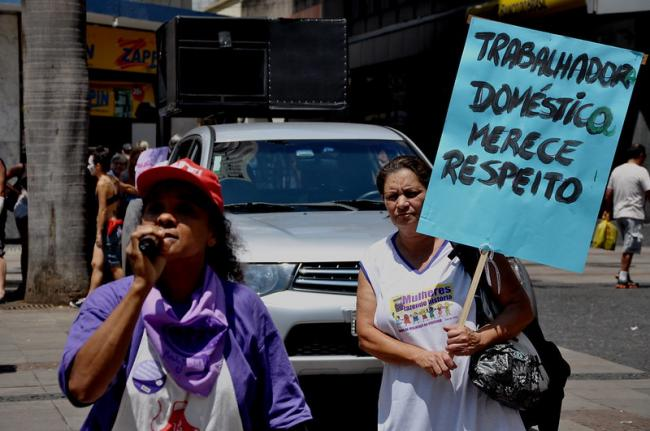 """A woman holds a sign reading """"Domestic workers deserve respect"""" during a demonstration in Campinas, Brazil in 2013 (Robson B. Sampaio, Flickr)."""