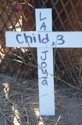 A cross commemorates a three-year-old child at the Eloy Detention Center vigil (Photo by Katharine Davies Samway)